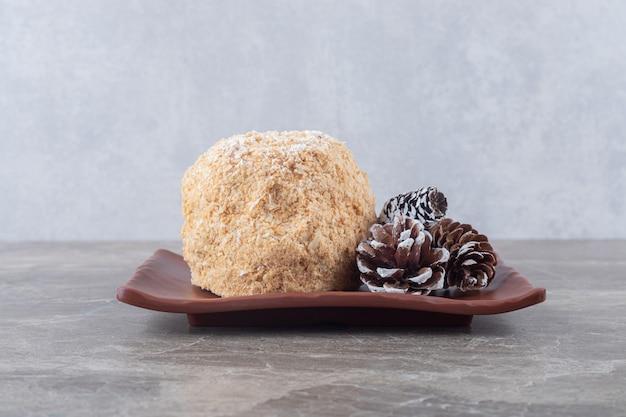 Dennenappels en een eekhoorncake op een bruine schotel op marmeren oppervlak