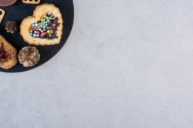 Dennenappels, koekjes, cakes en crackers op een zwart bord op marmeren tafel.