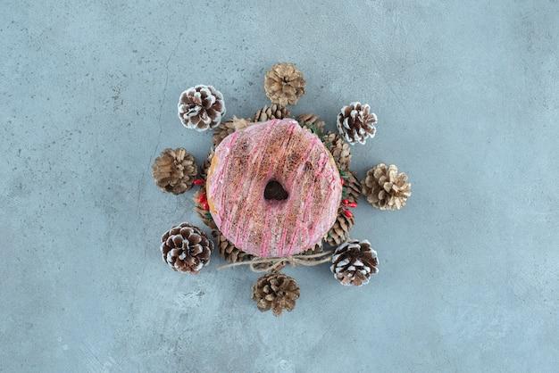 Dennenappels rond een donut op een krans op marmeren oppervlak