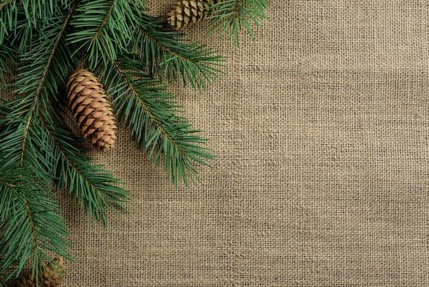 Dennenboomtakken en kegels liggen op de rand van een juteachtergrond. kerst achtergrond met kopie ruimte.