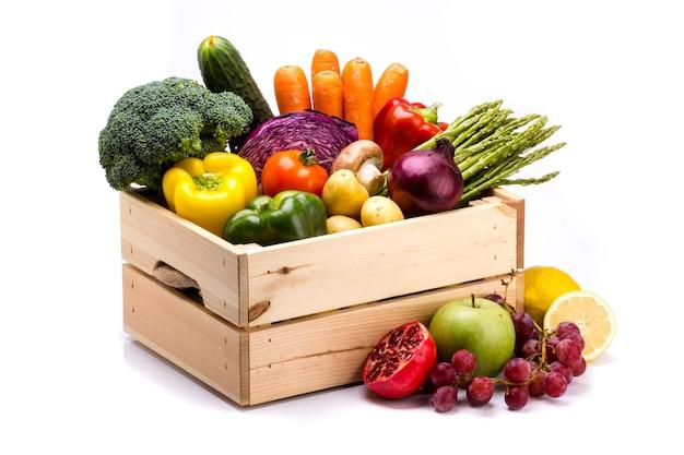 Dennenkist vol kleurrijke verse groenten op een witte achtergrond, ideaal voor een uitgebalanceerd dieet