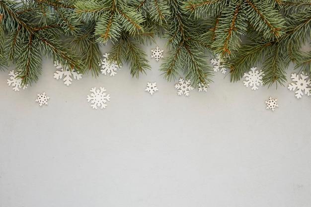 Dennennaalden op grijze achtergrond met sneeuwvlokken
