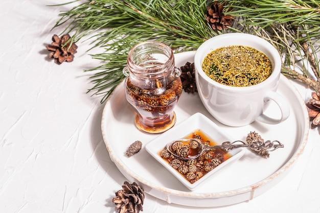 Dennennaaldthee, sollip-cha, traditionele koreaanse drank. dennenappeljam, alternatieve geneeskunde, gezonde levensstijl. witte stopverfachtergrond, kopieer ruimte