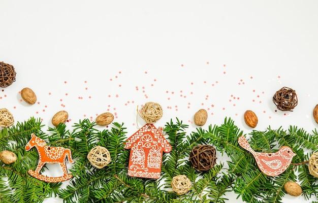 Dennentakken, geschenkdozen, houten speelgoed, steranijs, droge stukjes sinaasappel, decoratieve ballen en noten op een witte achtergrond. kopieer de ruimte, plat leggen. uitzicht van boven