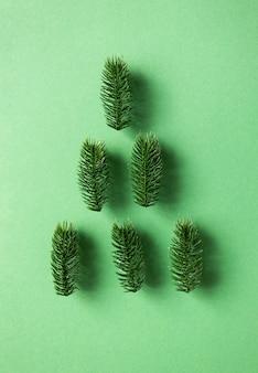 Dennentakken liggen in een minimalistische compositie in de vorm van een kerstboom