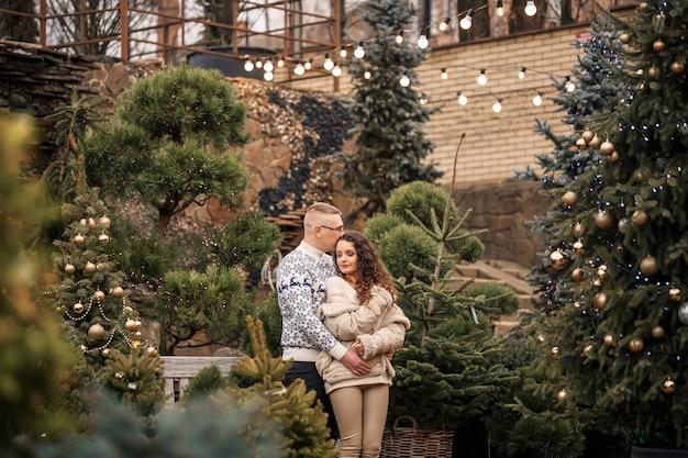 Dennentakken van de kerstboom. jong koppel versieren van een kerstboom buiten. kerstversiering, lolly's en ballen.