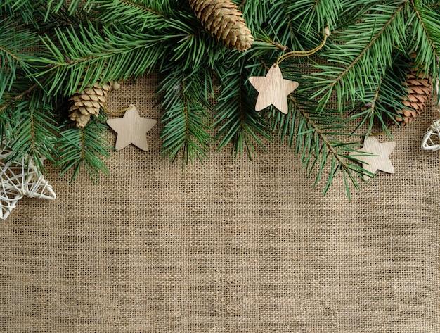 Dennentakken, versierd met houten kerstversieringen, liggen op een juteachtergrond met kopie ruimte.