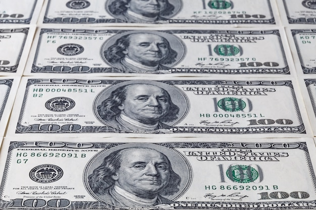 Denominaties van honderd amerikaanse dollars bladeren ver weg. achtergrond van dollars.