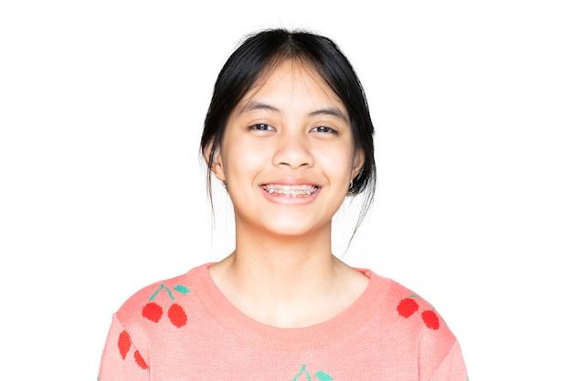 Dental brace girl glimlacht en kijkt naar de camera op een witte achtergrond, ze voelt zich gelukkig en heeft een goede houding met tandarts. motiveer kinderen niet bang als ze naar de tandheelkundige kliniek moeten.