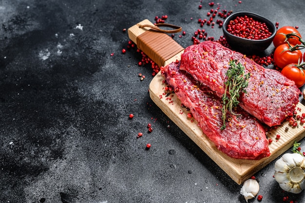 Denver steak op een snijplank. marmer rauw rundvlees. zwarte achtergrond. bovenaanzicht. kopieer ruimte.