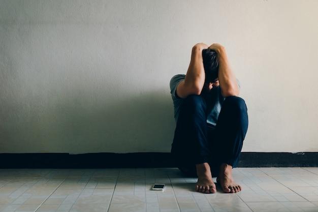 Depressie concept. man met depressie alleen zittend op de vloer in de donkere kamer