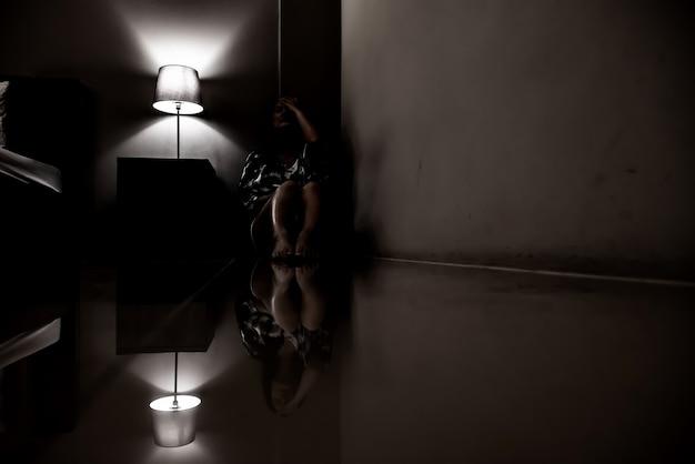 Depressie vrouw alleen in de donkere kamer. geestelijk gezondheidsprobleem, ptss is een posttraumatische stressstoornis.