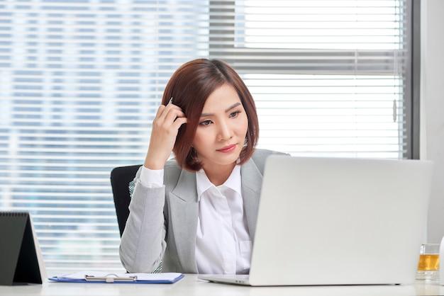 Depressief beklemtoonde jonge aziatische bedrijfsvrouw met laptop die aan problemen lijdt