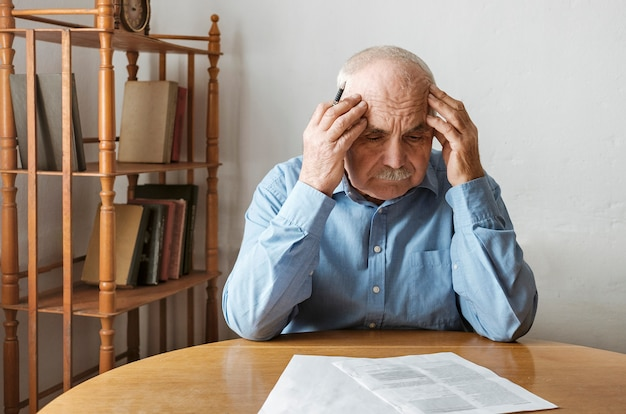 Depressief, bezorgde senior man die papierwerk doet