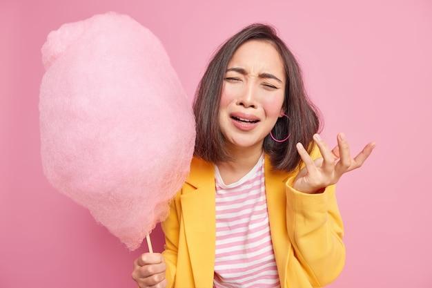 Depressief boos aziatische vrouw heeft neerslachtige gezichtsuitdrukking houdt smakelijke suikerspin op stok voelt zich ongelukkig na ruzie met vriend draagt modieuze gele jas geïsoleerd over gele muur