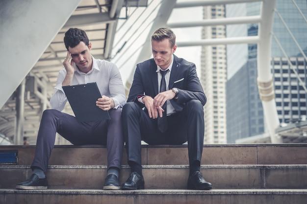Depressief en moe zakenman zitten in de stad