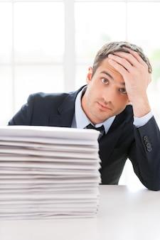 Depressief en overwerkt. depressieve jongeman in overhemd en stropdas die naar de camera kijkt en het hoofd in de hand houdt terwijl hij aan de tafel zit met een stapel documenten erop