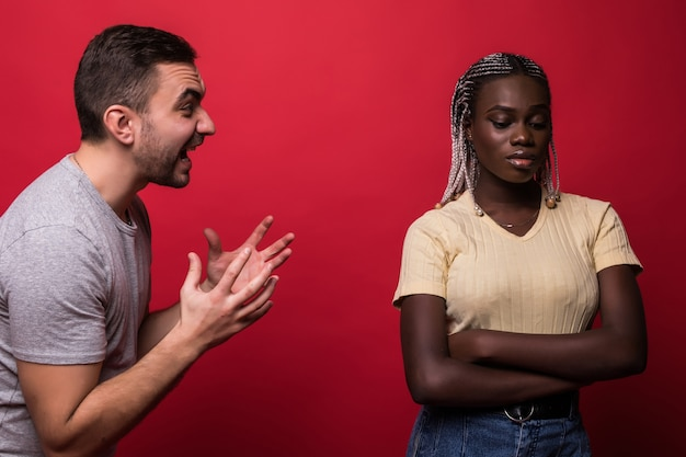 Depressief gemengd ras jong koppel na ruzie op rode achtergrond