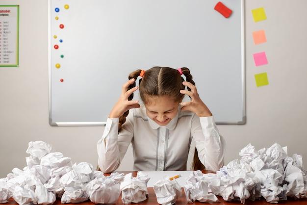 Depressief schoolmeisje dat hard denkt, probeert compositie te schrijven