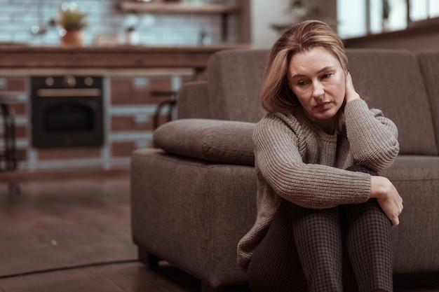 Depressief voelen. vrouw die een bruine, vierkante broek draagt, voelt zich depressief na werkproblemen