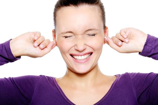 Depressief vrouwelijk gezicht dat de oren met vingers stopt