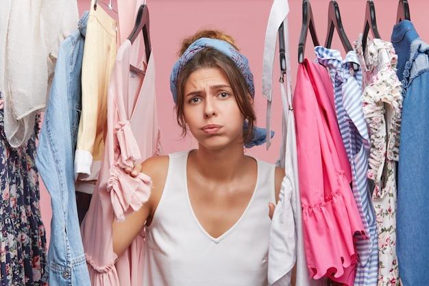 Depressief vrouwtje staat in de buurt van een kledingrek vol kleren, heeft een moeilijke keuze en weet niet wat ze moet aantrekken.