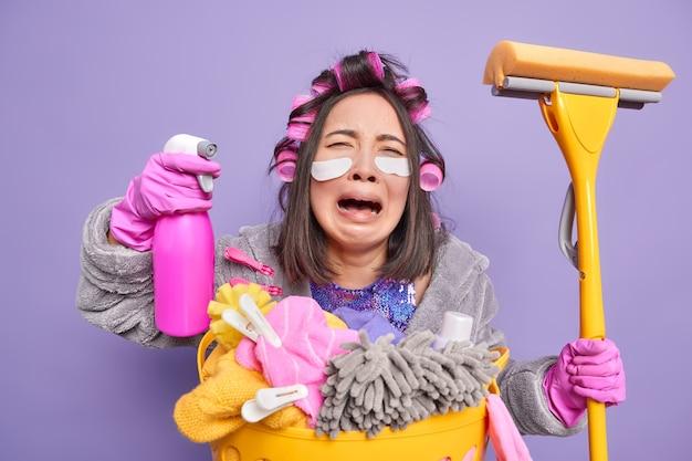 Depressieve aziatische huisvrouw huilt uit wanhoop drukt negatieve emoties uit past patches onder de ogen toe om fijne lijntjes te verminderen draagt haarrollers poseert in de buurt van wasmand geïsoleerd over paarse muur