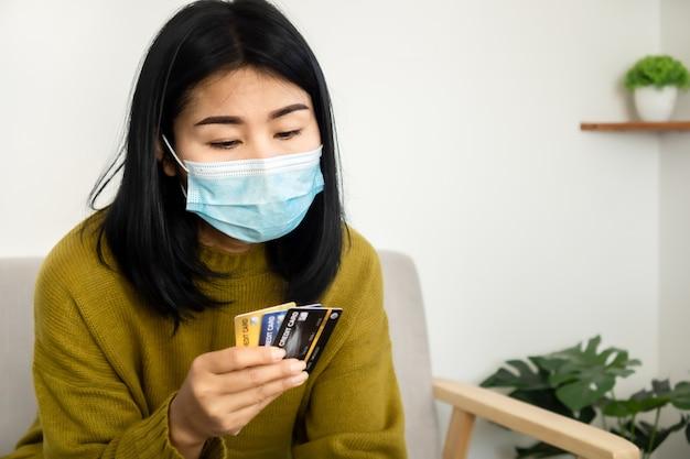 Depressieve aziatische vrouw met beschermend masker met creditcards