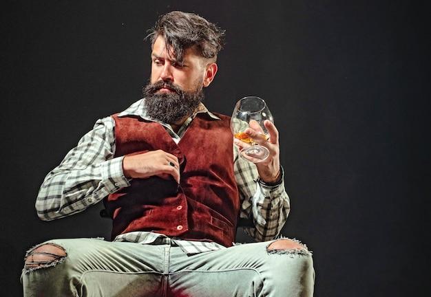 Depressieve bebaarde man in pak met glas alcohol