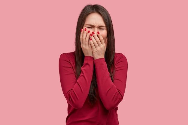 Depressieve brunette dame bedekt mond met handen, heeft een treurige uitdrukking, zwart haar, gekleed in rode kleren