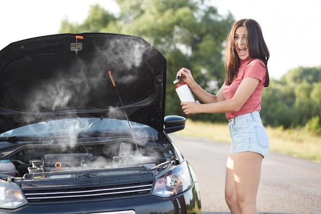 Depressieve brunette vrouwelijke bestuurder staat in de buurt van kapotte auto met geopende motorkap, probeert zelf een technisch probleem op te lossen terwijl ze op autotechnicus wacht, mond wijd open, roept wanhopig uit