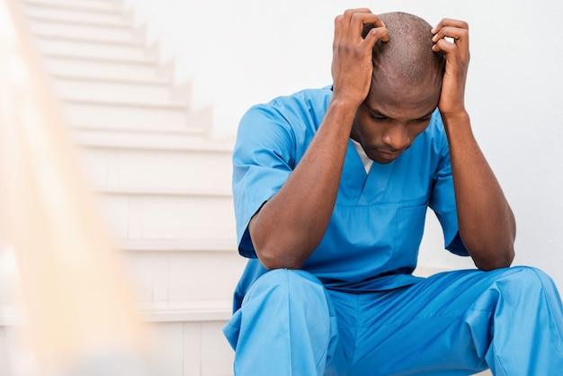 Depressieve chirurg. depressieve jonge afrikaanse arts in blauw uniform die zijn hoofd met handen aanraakt en wegkijkt terwijl hij aan de trap zit
