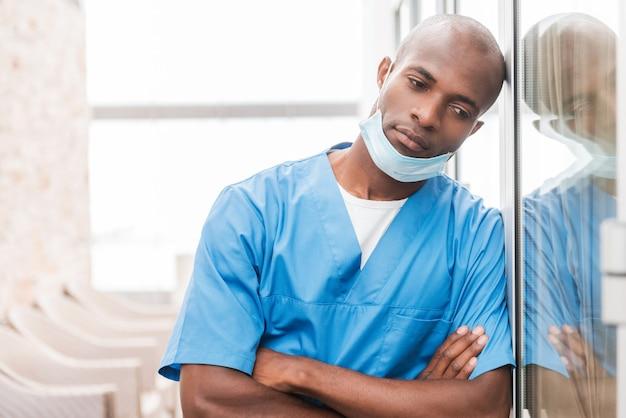 Depressieve chirurg. depressieve jonge afrikaanse arts in blauw uniform houdt de armen gekruist en kijkt weg terwijl hij tegen de glazen deur leunt