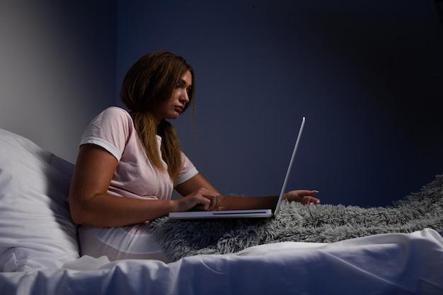 Depressieve ernstige vrouw die in bed zit en op laptop werkt.