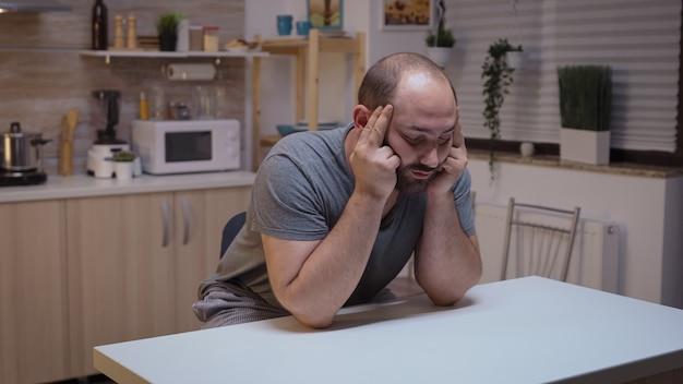 Depressieve gestresste man zit aan de tafel met hoofdpijn. vermoeid ongelukkig ziek bezorgd onwel persoon die lijdt aan migraine, depressie, ziekte en angst zich uitgeput voelen met symptomen van duizeligheid