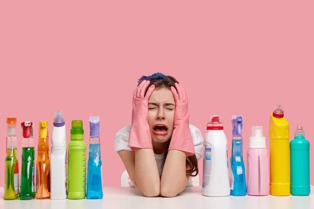 Depressieve huilende vrouw kijkt stressvol, houdt beide handen op het hoofd, draagt beschermende handschoenen