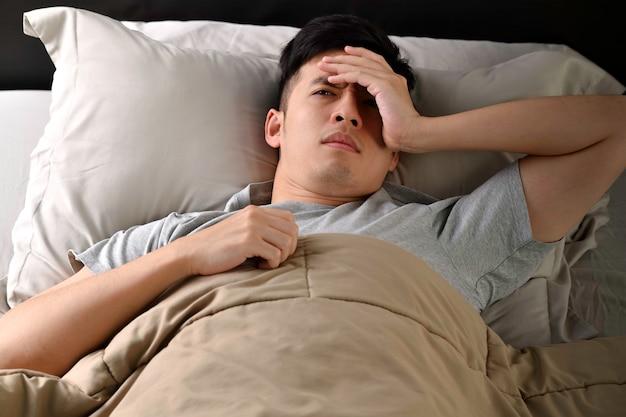 Depressieve jonge aziatische man die in bed ligt kan niet slapen van slapeloosheid