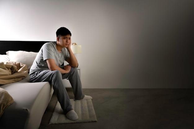 Depressieve jonge aziatische man die in bed zit kan niet slapen van slapeloosheid
