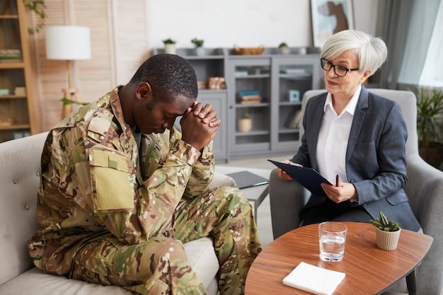 Depressieve jonge militaire man zittend op de bank tijdens therapiesessie met psycholoog