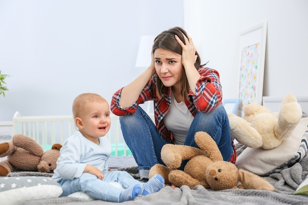 Depressieve jonge vrouw met schattige baby thuis