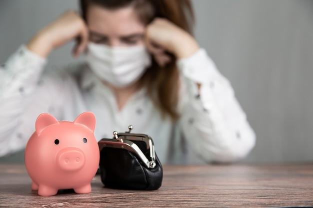 Depressieve jonge vrouwelijke zakenvrouw met roze spaarvarken om te sparen en een veiligheidsmasker voor covid-19 te dragen