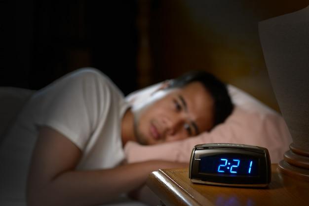 Depressieve man die lijden aan slapeloosheid in bed liggen