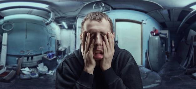 Depressieve man met handpalmen op zijn wangen boven kelder