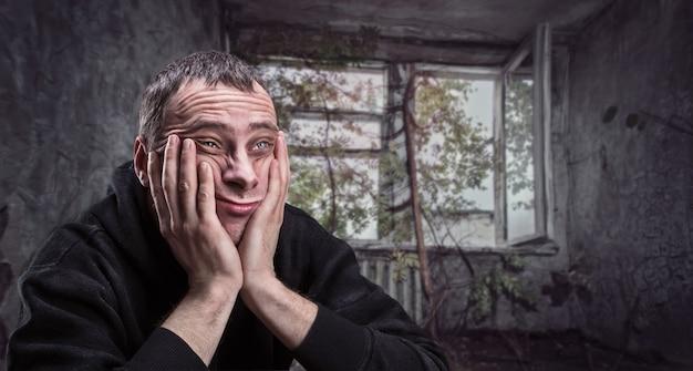 Depressieve man met handpalmen op zijn wangen denkt in een oud getto-appartement
