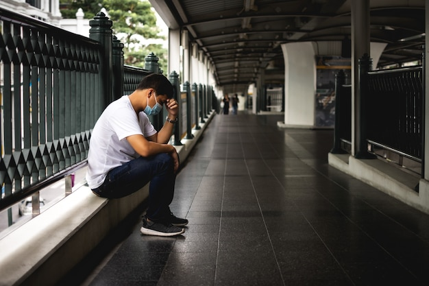 Depressieve man zit op de loopbrug van het pad van het hemeltreinstation trieste man eenzaam en ongelukkig concept