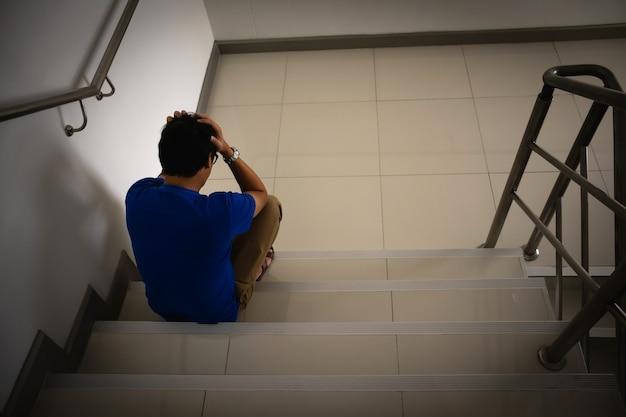 Depressieve man zit op de trap van het woongebouw trieste man eenzaam en ongelukkig concept