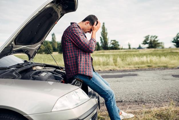 Depressieve man zit op een motorkap van een kapotte auto. voertuig met open motorkap langs de weg