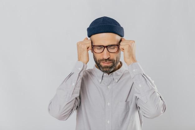 Depressieve ongeschoren jonge man lijdt aan hoofdpijn, houdt handen in vuisten in de buurt van tempels, sluit ogen