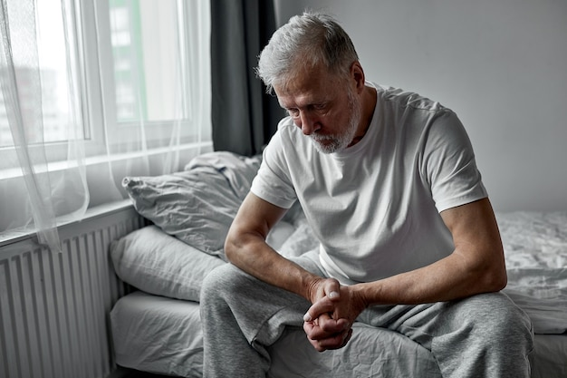 Depressieve senior man zit bedachtzaam naar beneden te kijken, melancholische man alleen thuis