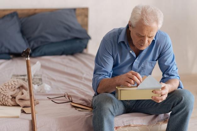 Depressieve, trieste bejaarde man die een doos met post vasthoudt en zijn eigen oude brieven omdraait terwijl hij zich zijn jeugd herinnert